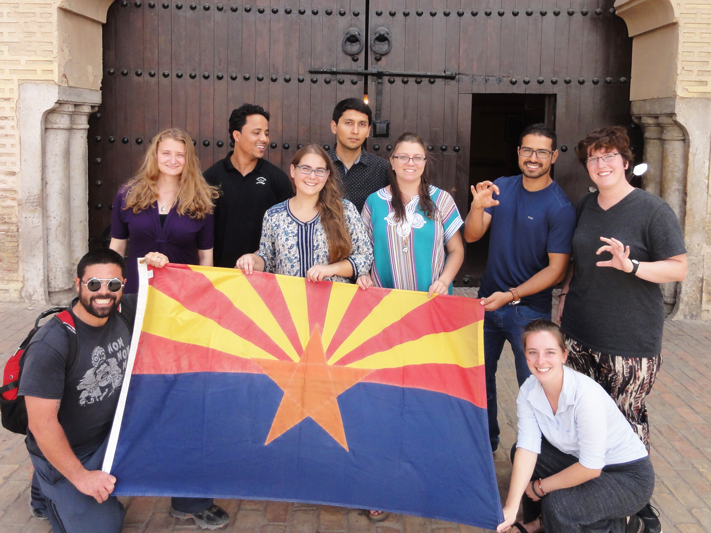 Arizona Arabic Flagship students during a study abroad trip to Meknes, Morocco, before COVID-19. Nine students are holding an Arizona flag.