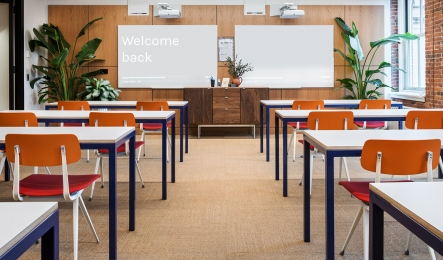 "WeWork space with desks and a whiteboard with the words ""Welcome Back"" written on it."