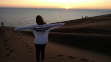 Student wearing white wildcats shirt on beach at sunset