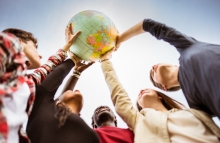 students cooperating to hold a globe up towards the sky