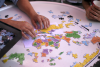 UArizona international students putting together a global map puzzle in the Global Center courtyard