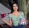 Valeria M, 2021 scholarship raffle winner, holding a Bear Down flag and a UArizona Block A sign
