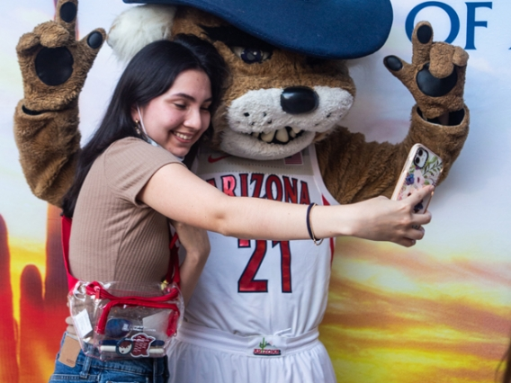 International students takes a selfie with Wilbur Wildcat at the 2021 Global Wildcat Welcome Party