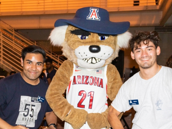 Two International students take a photo with Wilbur Wildcat at the 2021 Global Wildcat Welcome Party