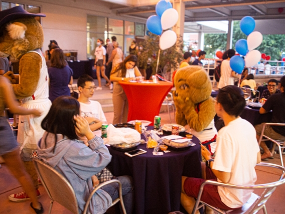 International students playing a table game with Wilma Wildcat at the 2021 Global Wildcat Welcome Party