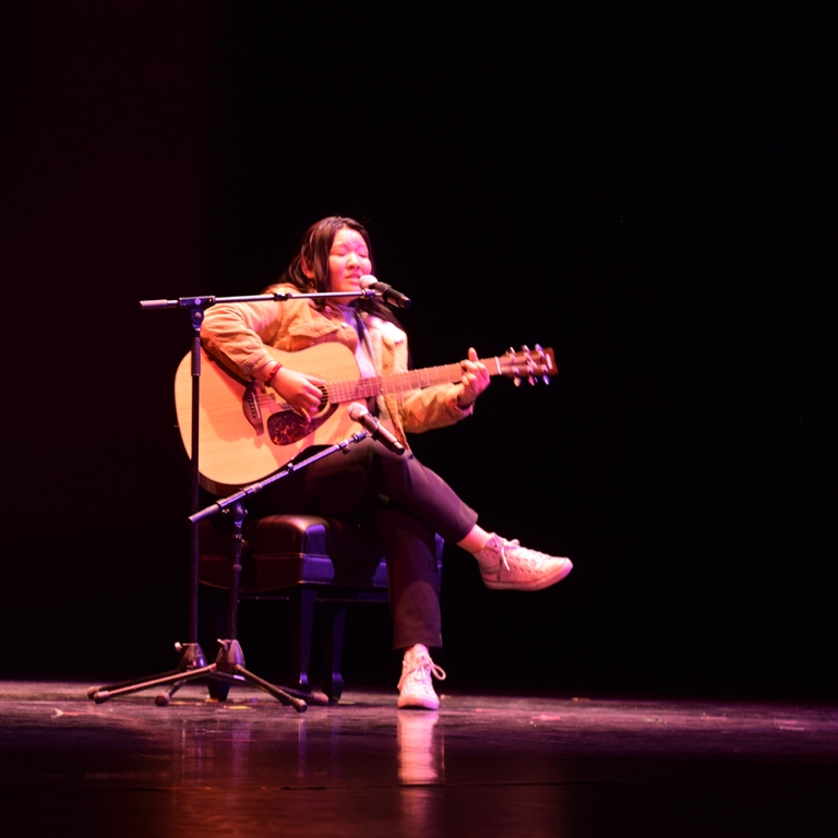Seated female playing guitar at Global Wildcats Got Talent