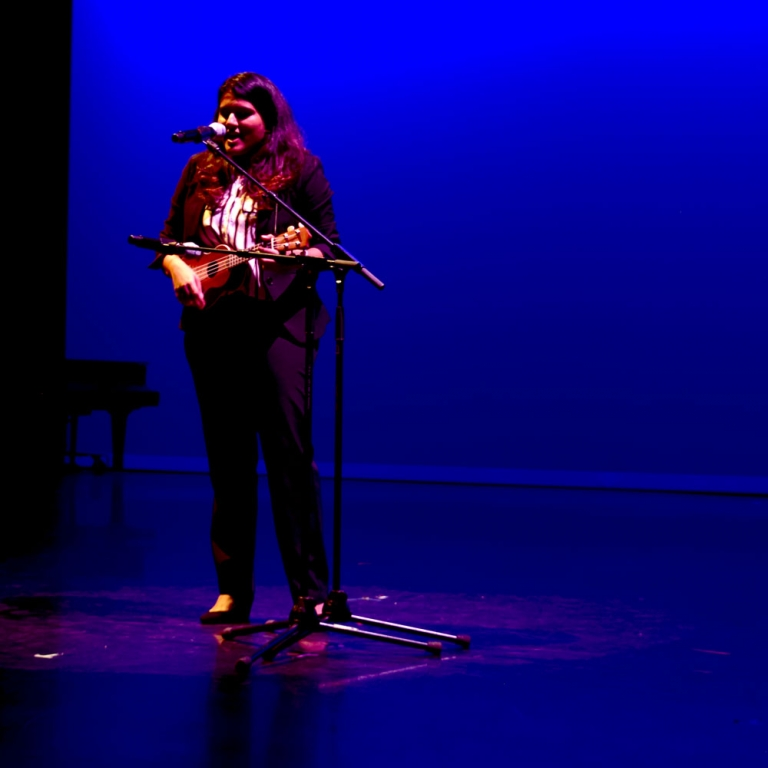 Female performer on ukulele at Global Wildcats Got Talent