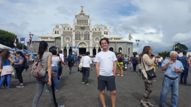 UA Study Abroad Student Brenden Barness standing in a populated town square in Costa Rica with a Basilica behind him