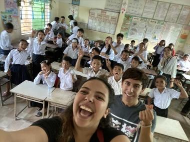 UA Study Abroad Student Reina Salgado taking selfie with elementary school students in classroom, on GEL program in Southeast Asia.