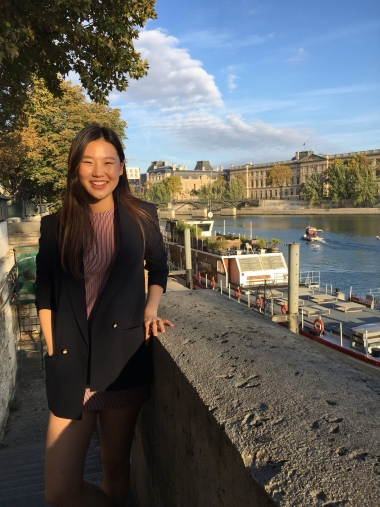 UA Study Abroad Student Stephanie Kim standing with a view of the Seine in Paris behind her.