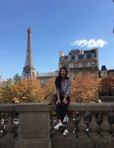 UA Study Abroad Student Stephanie Kim sitting on a wall in Paris with the Eiffel Tower in the background.