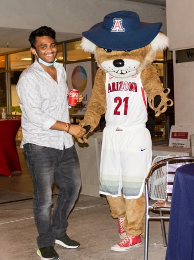 International student shakes hand with Wilbur Wildcat at the 2021 Global Wildcat Welcome Party