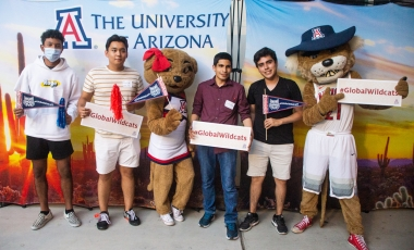 International students holding #GlobalWildcats signs with Wilma and Wilbur Wildcat at the 2021 Global Wildcat Welcome Party