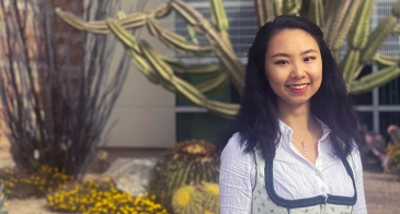 Student Mandy Han in front of UArizona Student Union, with cactus in background