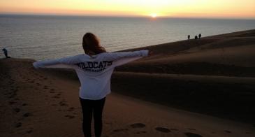 Student wearing white wildcats shirt on beach at sunset