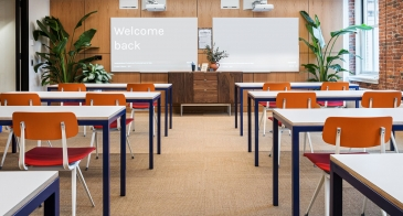 """WeWork space with desks and a whiteboard with the words """"Welcome Back"""" written on it."""